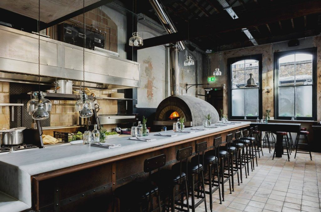 Urban bar with wood-fired pizza and gin distillery