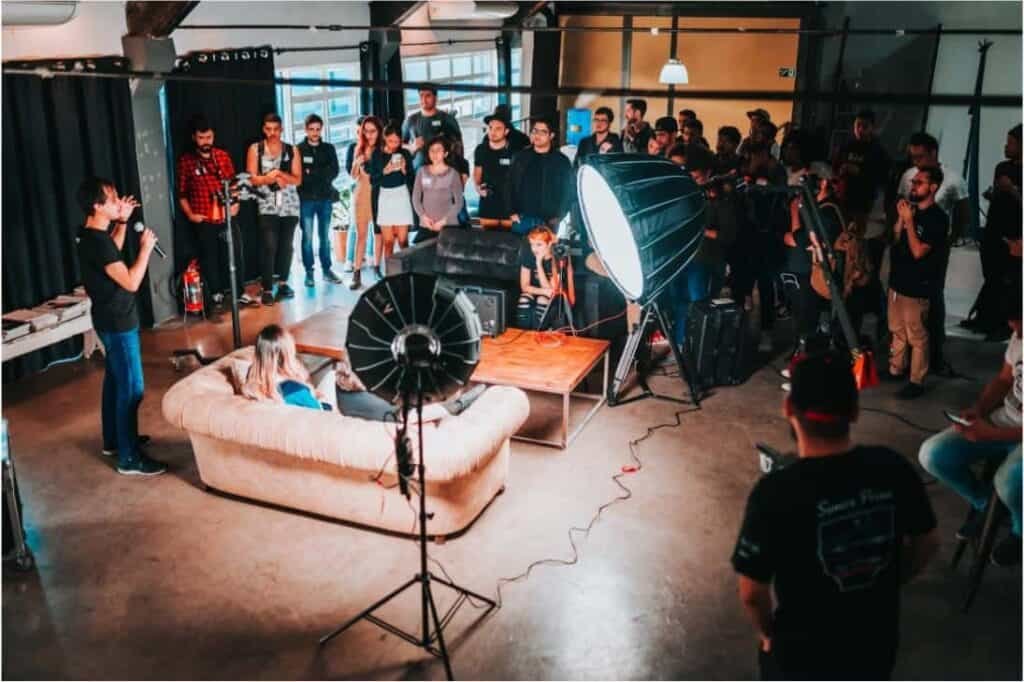 People discussing topics in an event set-up with guests in sofas and an audience