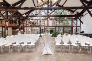 Luminous loft with glass roof, wooden beams and white interior.