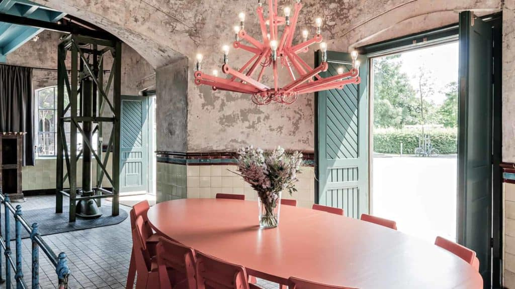 Industrial warehouse with raw industrial walls, pastel pink and green accents