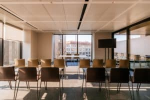 Bright venue with a cosy atmosphere featuring floor-to-ceiling windows and high ceilings.
