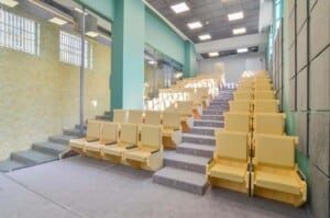 Colourful and quirky auditorium with a retro touch featuring wooden seats and radiant blue walls.