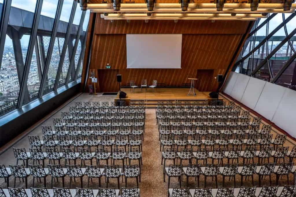 Spacious conference venue with floor-to-ceiling windows and a view of Paris