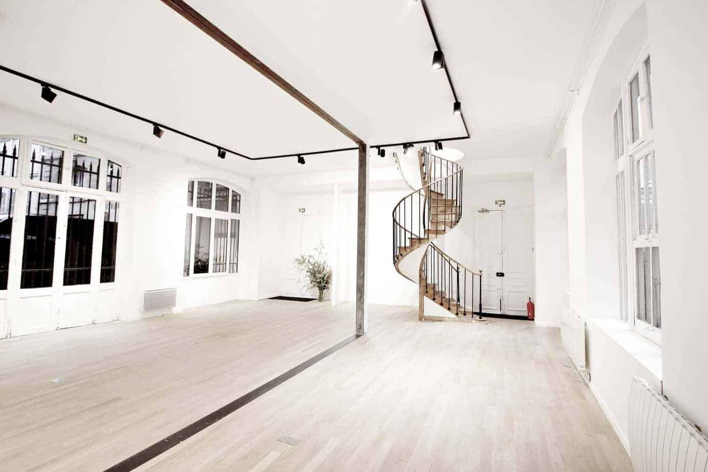 White gallery with light parquet flooring, white walls and large windows