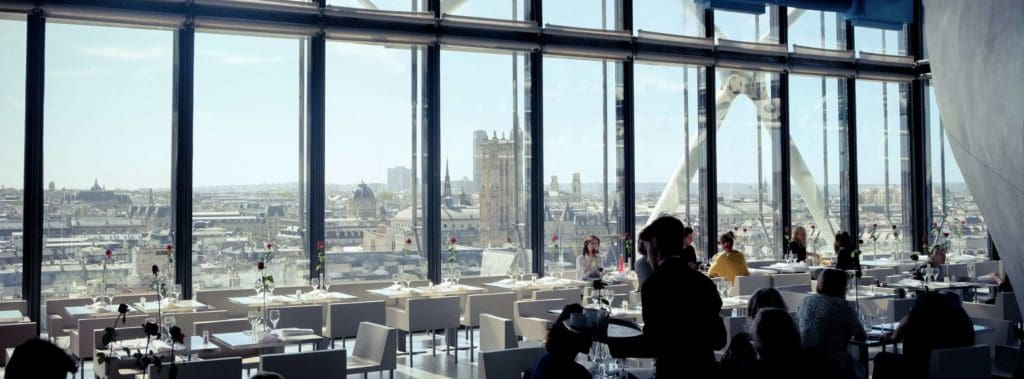 Restaurant with floor-to-ceiling windows offering a view of Paris