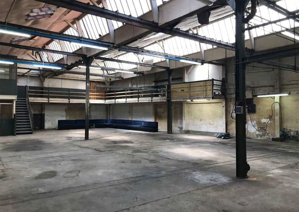 Open event space with concrete floor and industrial poles