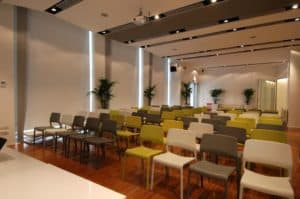 Luminous event space with a modern look featuring high ceilings and polished wooden floors.