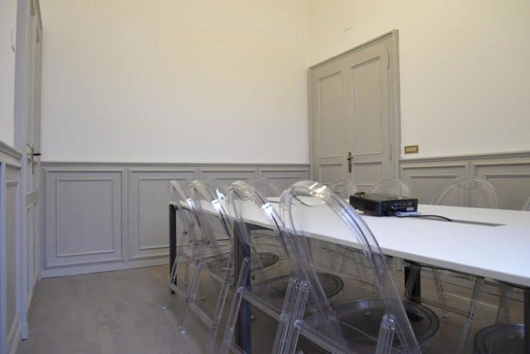 Sleek meeting room near Milan's central station featuring parquet floors and high ceilings.