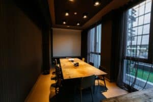 Stylish meeting room with a rustic touch featuring dark tones and wooden furniture.