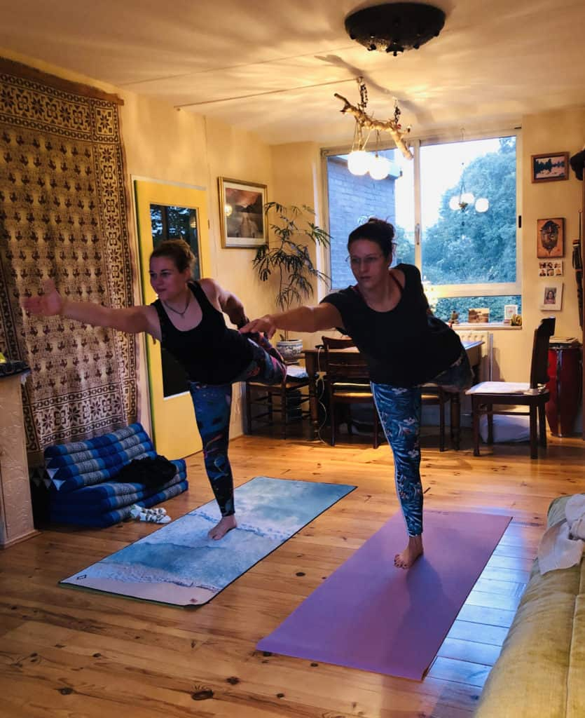 Two women practising yoga in a cottage