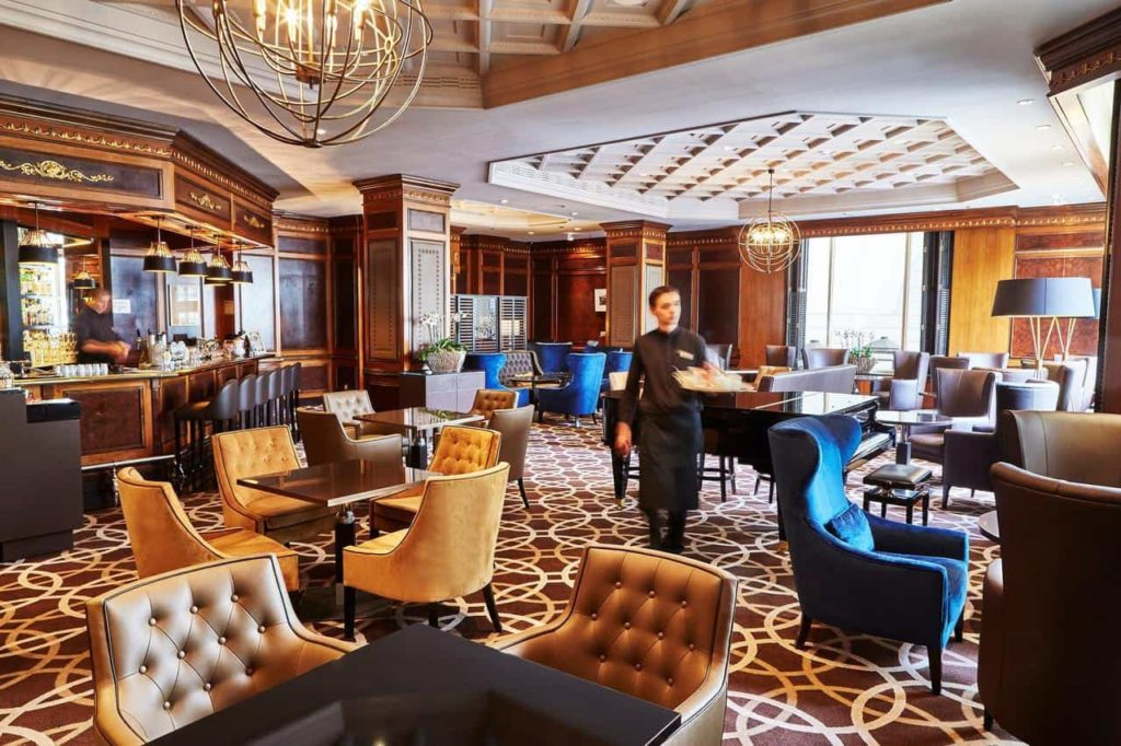 Historic and classical hotel lobby with chandeliers, luxurious carpet and authentic sofas