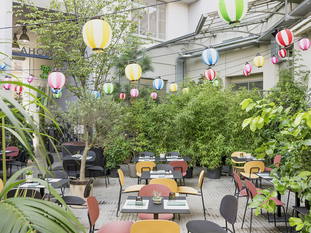 Vibrant courtyard terrace in Porta Genova decorated with plants and colourful furniture.