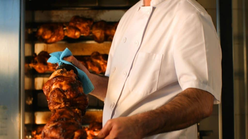 Chef holding a roasted chicken