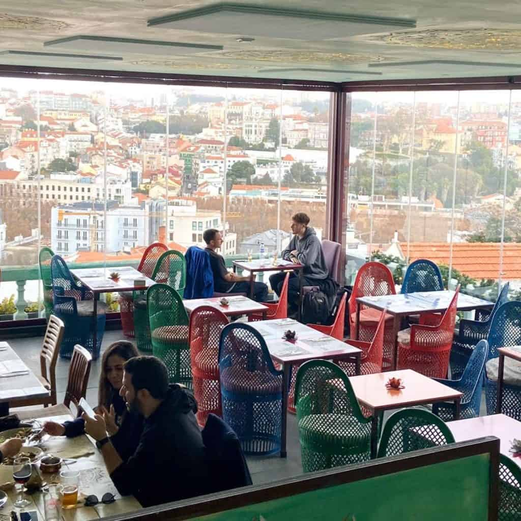 Friends dining in a restaurant with a view of Lisbon