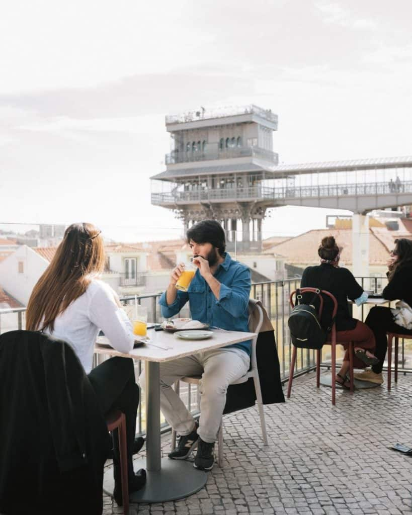 Couple enjoying a drink on a rooftop terrace with a view in Lisbon