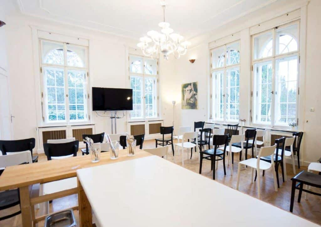 White and elegant workshop room with a chandelier and parquet flooring