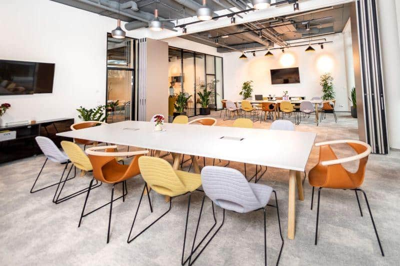 Modern and industrial meeting space with colourful chairs