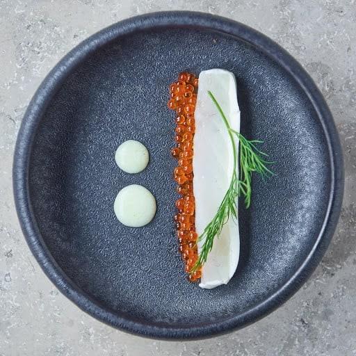 elegant dish with caviar on a grey plate