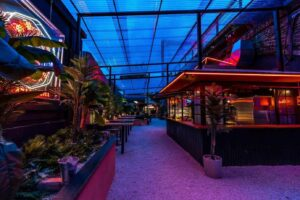 Hip and upbeat venue for celebrations featuring neon lights and serene green décor.